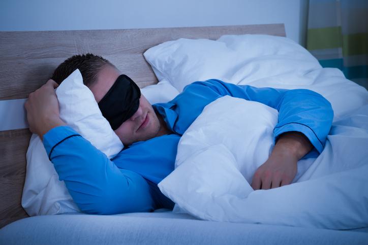 homem dormindo com uma máscara de sono