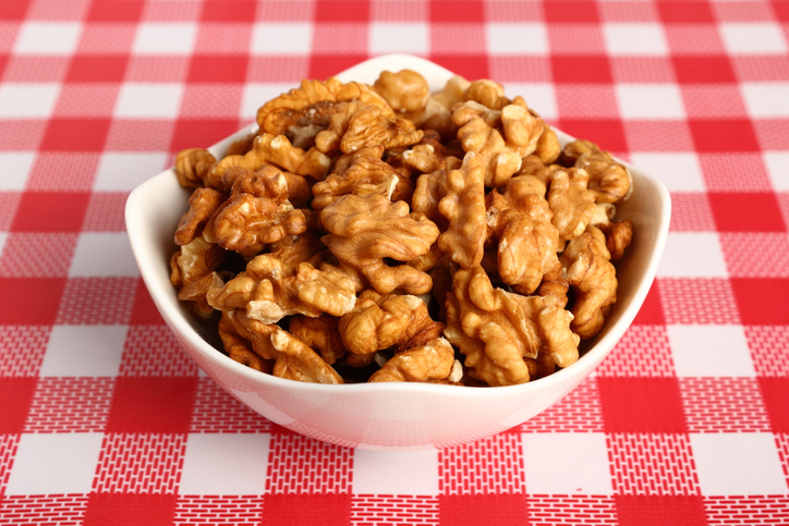 shelled walnuts in a bowl on a red checkered table cloth