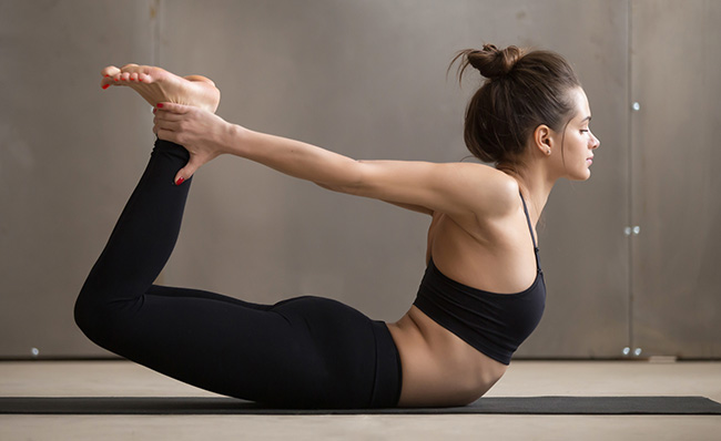 Bow pose for bloating