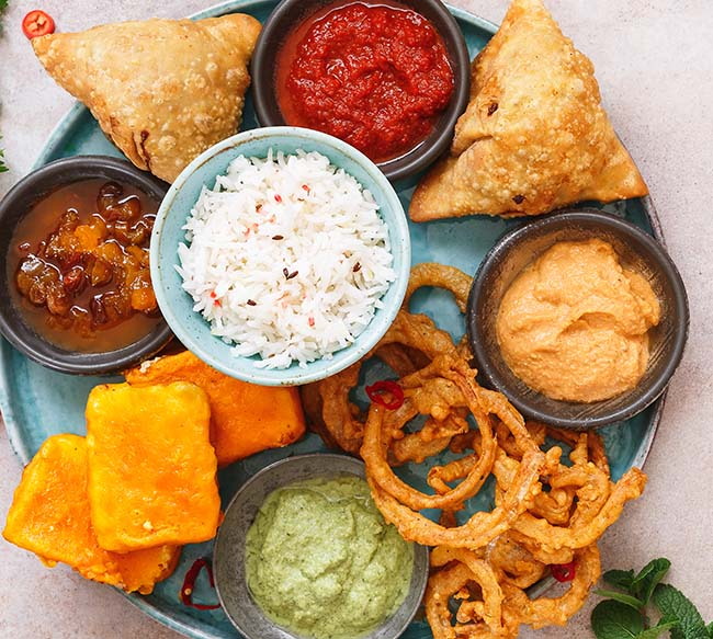 Indian vegan thali  with rice, different snacks and dips