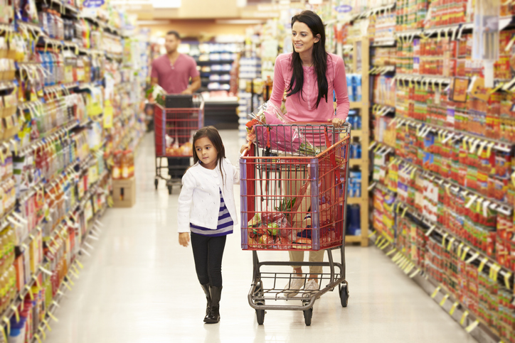 a mother and daughter walk down a grocery store aisle pushing a shopping cart