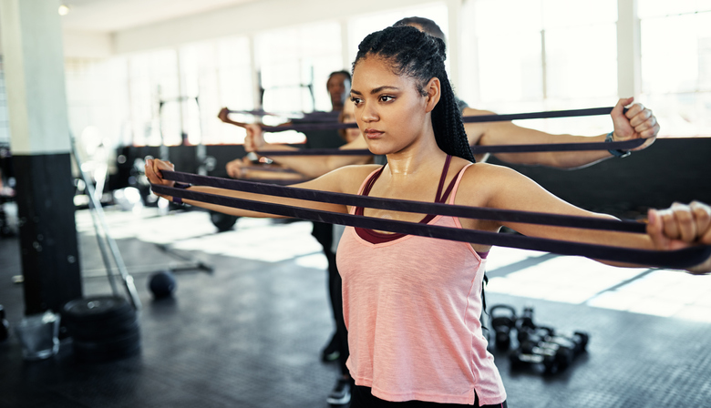 A woman uses a resistance band in an exercise class.