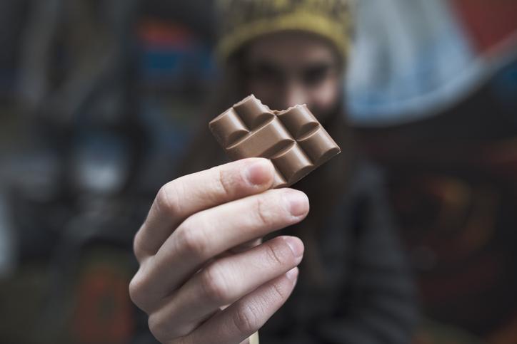 close up on a woman's hands holding a bitten piece of chocolate bar