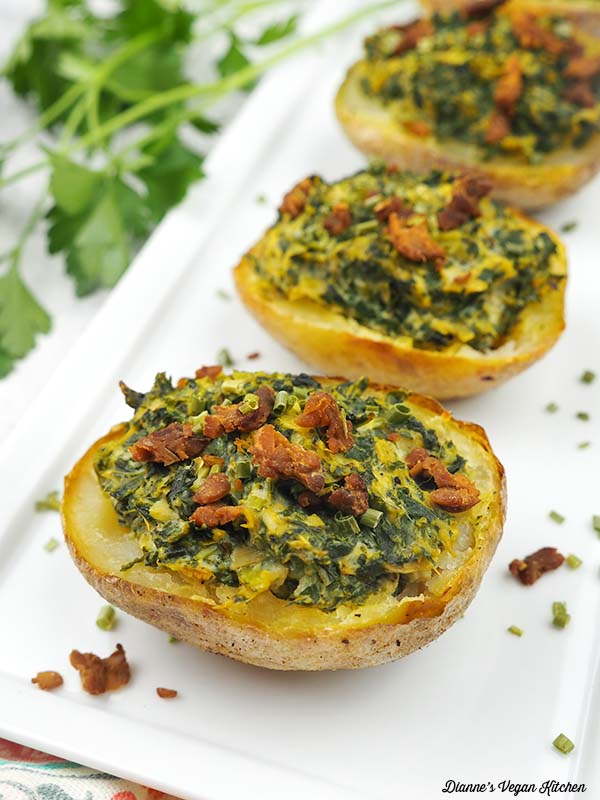 white serving tray with spinach baked potato skins topped with tempeh bacon