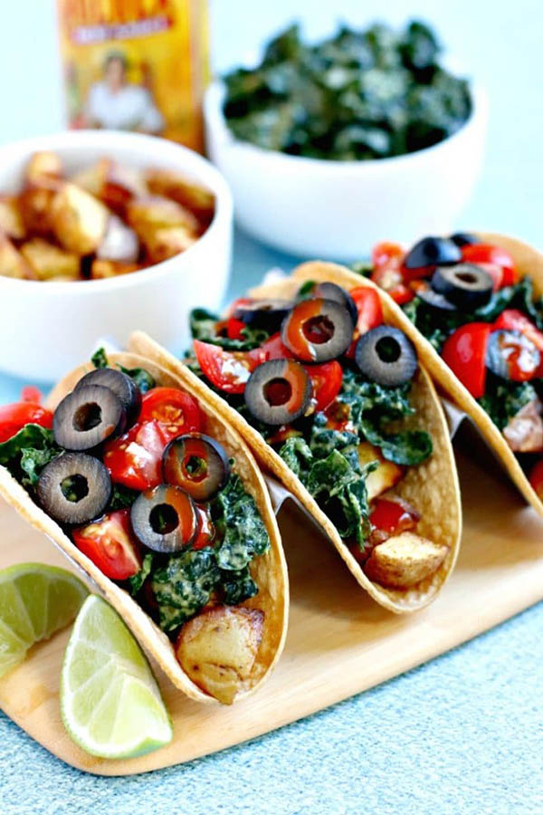 vegan potato tacos on a serving platter with roasted potatoes and kale salad in the background