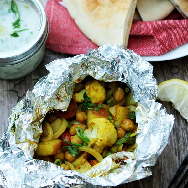 cauliflower grill packet with potatoes on a picnic table with pita bread and vegan yogurt sauce on the side