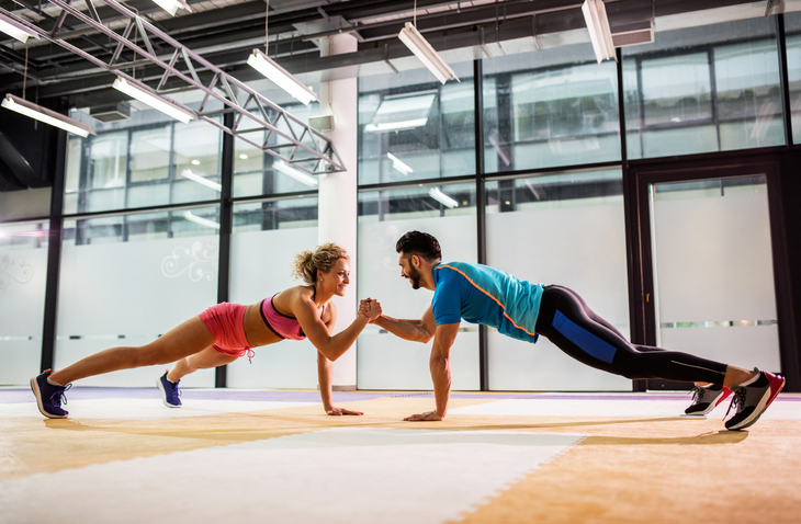 couple high-fiving while doing planks