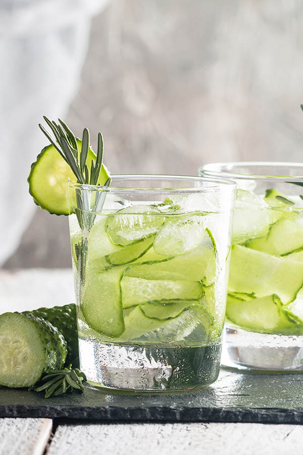 Glasses with fresh organic detox cucumber water on white wooden table
