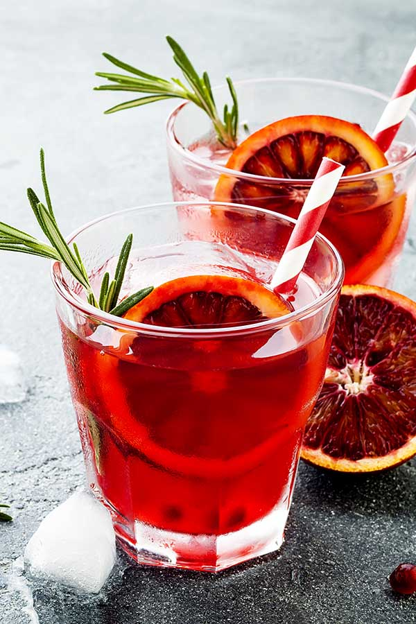 glass of blood orange and rosemary water on gray stone