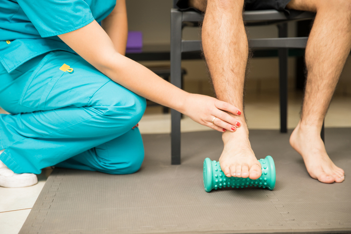 therapist assisting patient to use a foot roller for plantar fasciitis