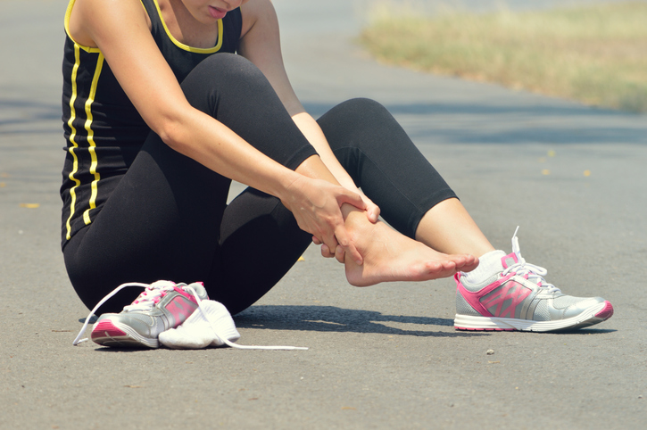 woman experiencing foot pain during a workout