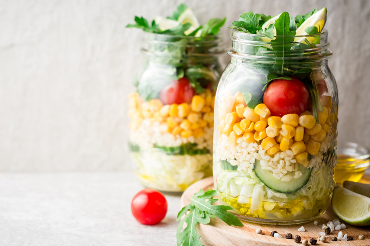 Healthy homemade salads with bulgur, vegetables and lime in mason jars
