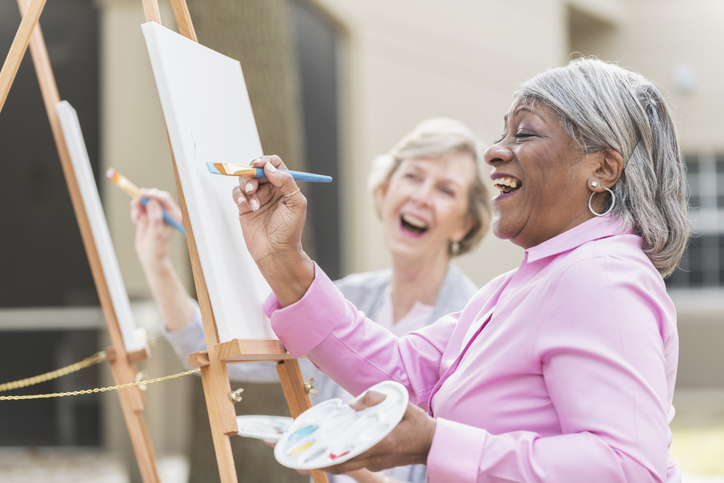 senior women painting and smiling