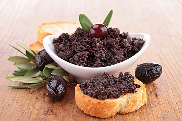 olive tapenade in a bowl and spread on bread
