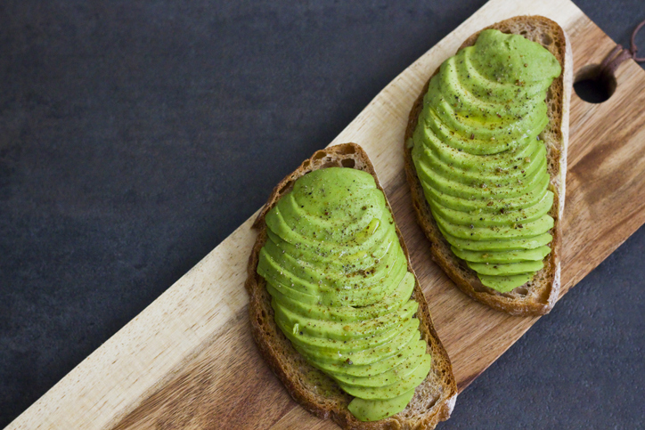 Two pieces of avocado toast on a wooden board.