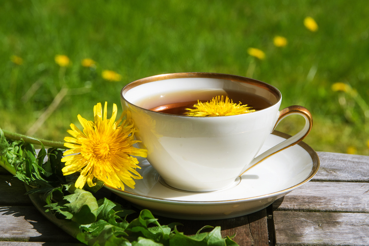 Dandelion tea in a white cup on a wooden table