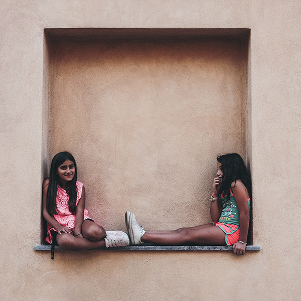 friends sitting together in a windowsill