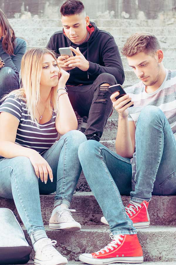 A girl is feeling completely alone, ignored by her smartphone obsessed friends