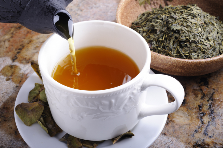 Green tea being poured into a cup next to loose tea