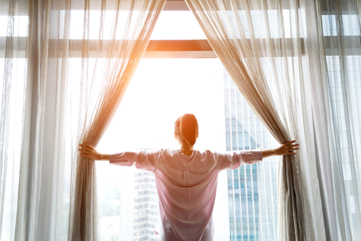 Woman opening curtains and looking out in the morning