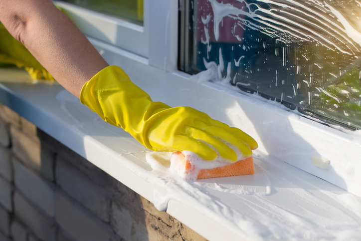 person washes a window sill outside the house