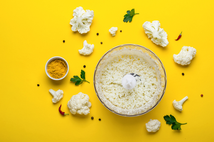 Blender bowl with freshly prepared cauliflower rice and spices on yellow background