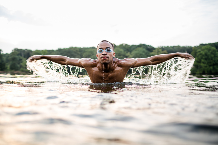 Young African Man Swimming In Lake