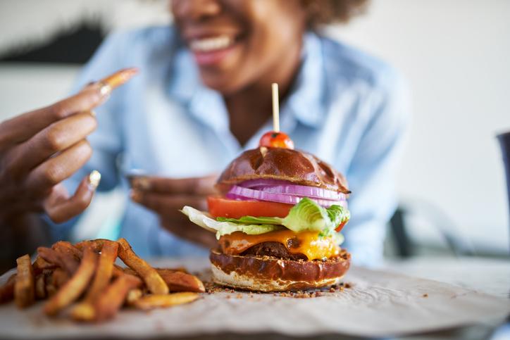 woman eating a vegan veggie burger with fries