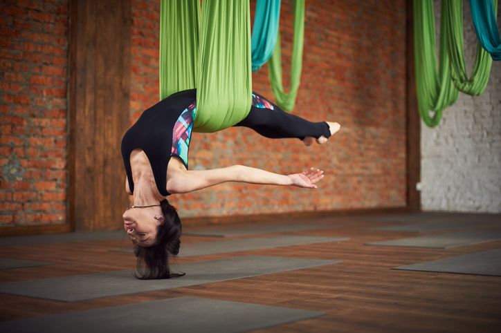 Young woman making antigravity yoga exercises in a loft interior