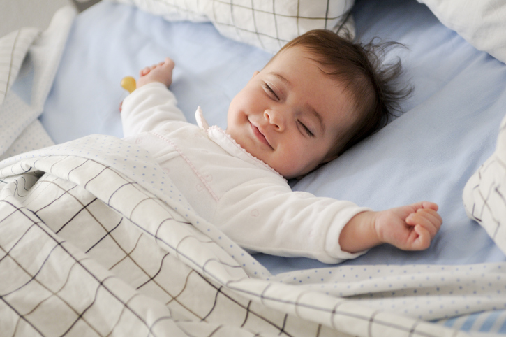 Smiling baby lying on a bed sleeping