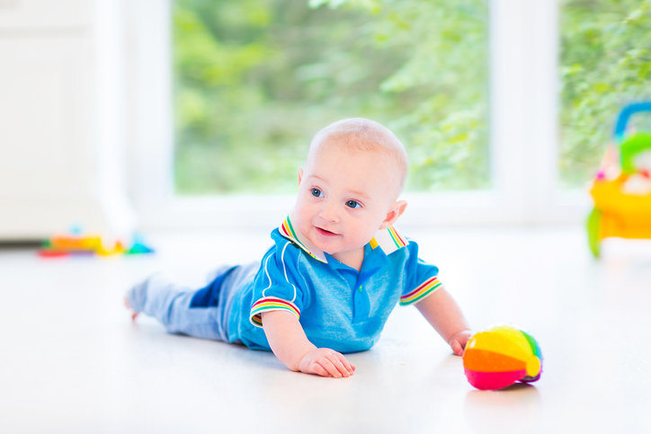 A baby plays with toys during tummy time.