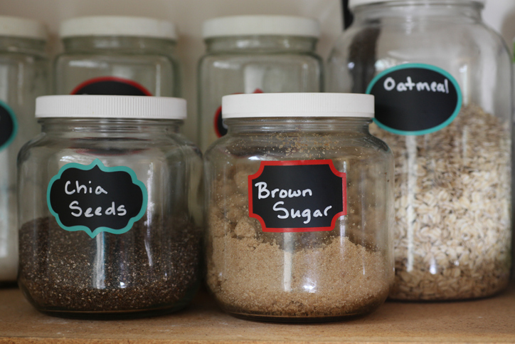 pantry glass jars filled with kitchen staples, including oatmeal, brown sugar and chia seeds on a shelf