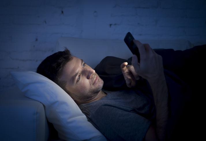man using cellphone in the dark