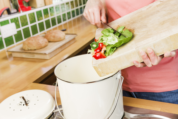 woman using a kitchen knife to scrape fruit and vegetable waste into a compost bin