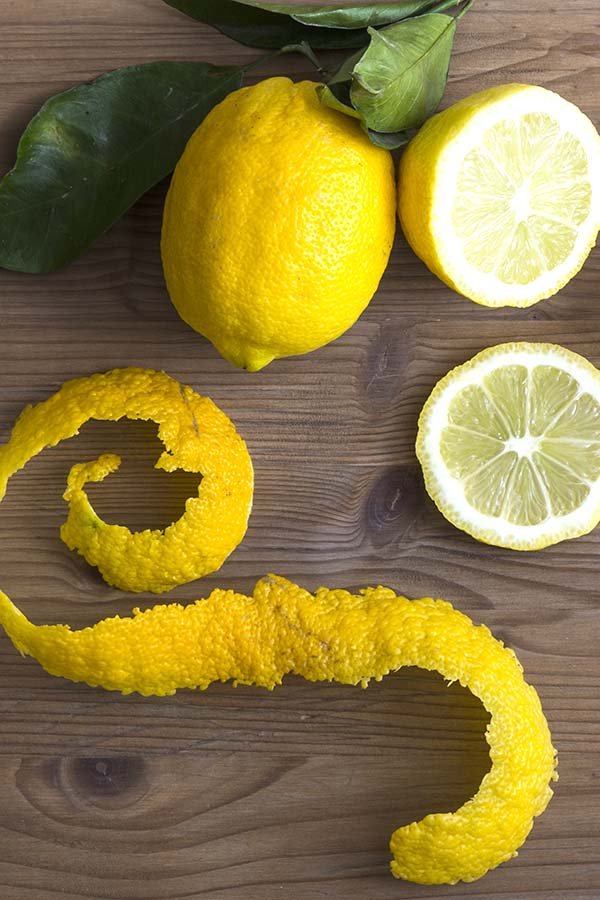 Lemon slices and peel on a wooden surface.