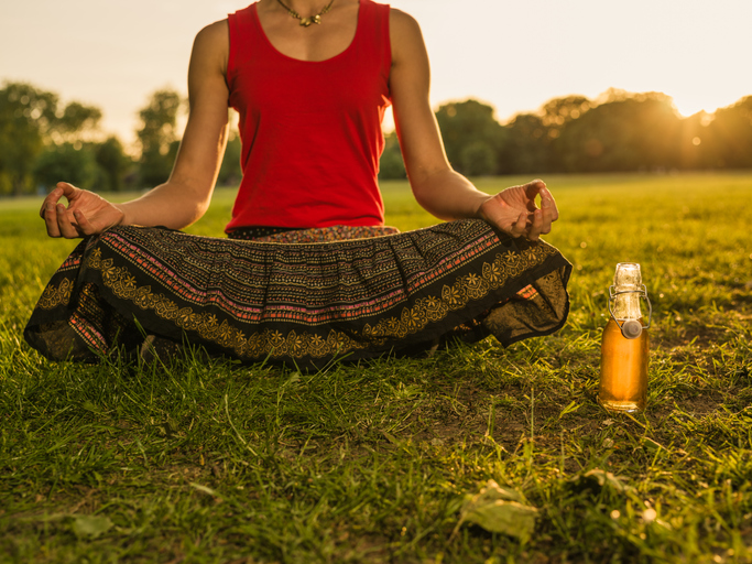 A young woman is meditating in a park at sunset, there is a bottle of wine next to her