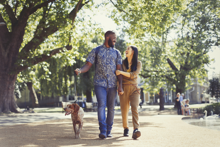 Couple walking dog in park