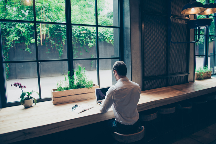 Rear view of a journalist stylish guy writing a story in a workplace in loft styled coworking, well dressed, sitting near window with view of garden