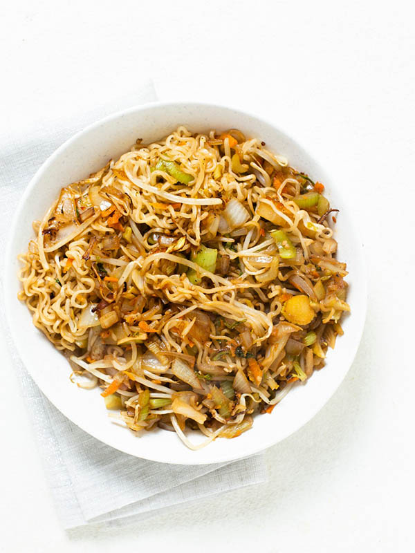 white bowl of vegetable chow mein on a white tabletop