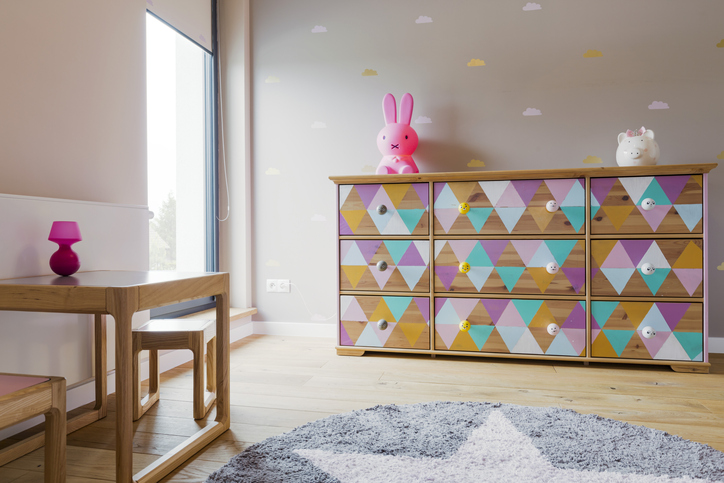 kid's bedroom with a large chest of drawers decorated in pastel triangles