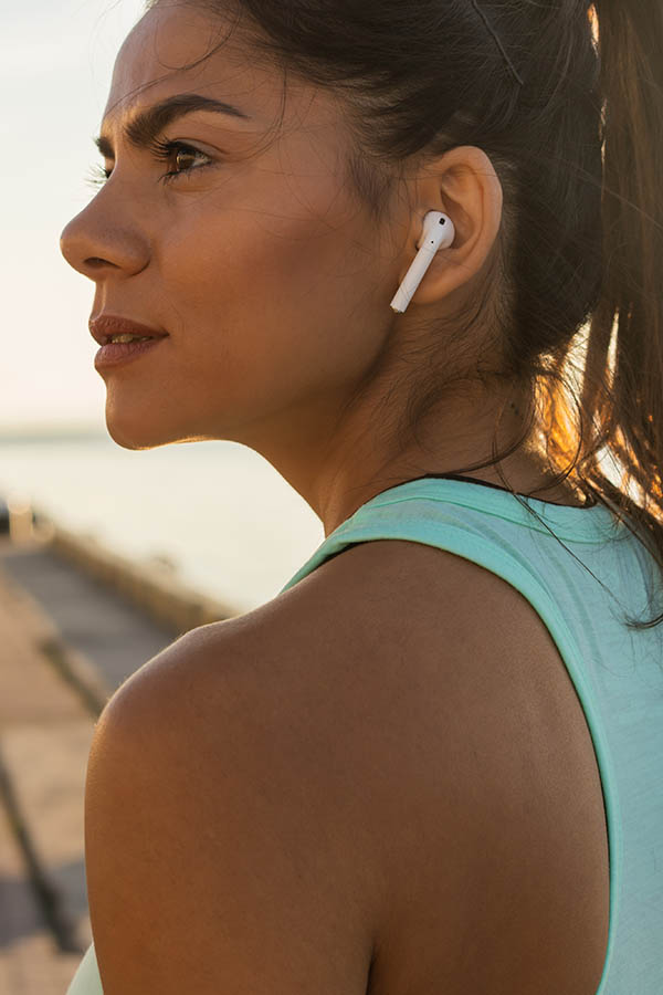 Tired fitness woman sweating taking a break listening to music on phone after difficult training. Young woman listening to music with earbuds