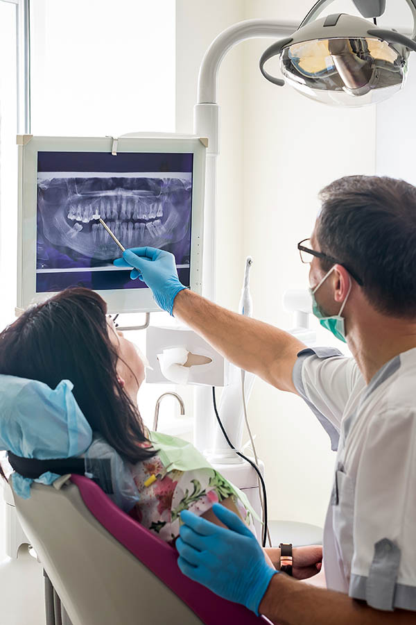Doctor dentist showing patient's gums on X-ray