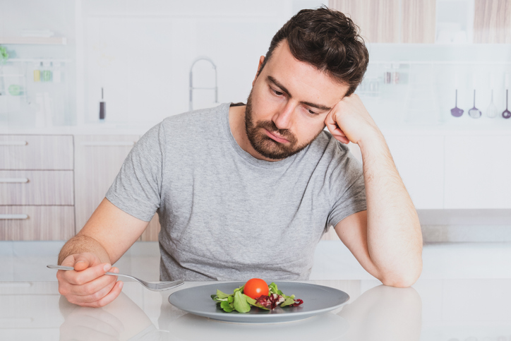 man looking reluctantly at a small salad