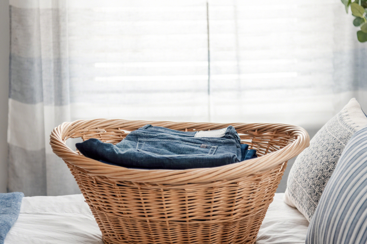 Wicker laundry basket with neatly folded jeans on the bed