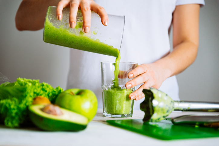 person making a green smoothie