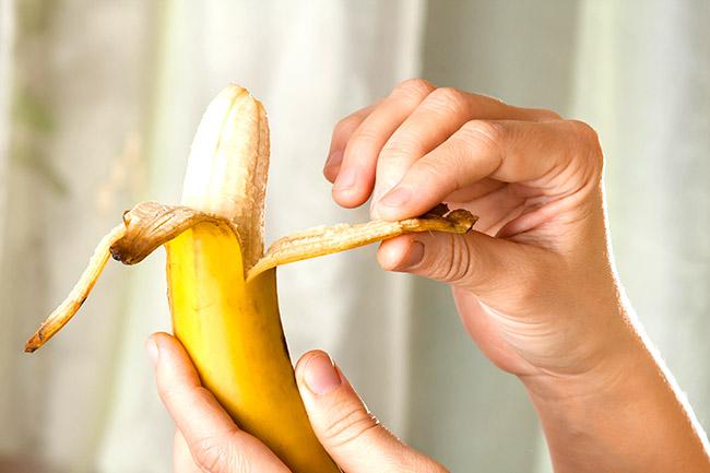 hands peeling ripe yellow banana, close up