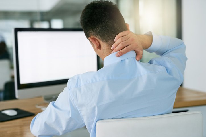 man sitting at desk holding pain in his neck