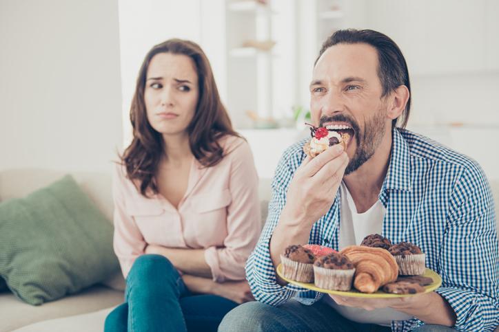 man eating sugary treats while woman looks at him judgementally