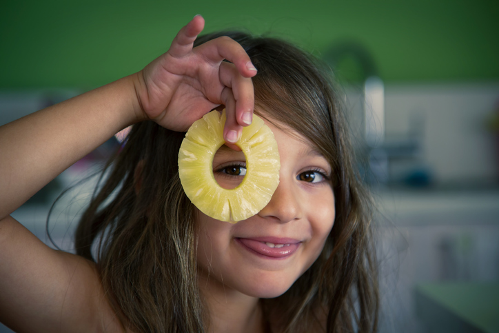 A young girl is peeking through the hole of a pineapple slice.