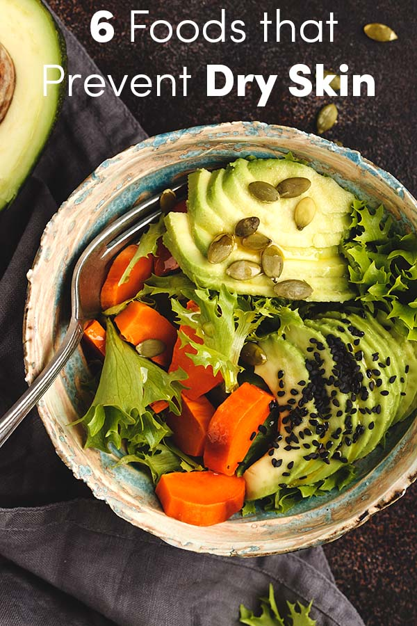 rainbow bowl with baked sweet potato and avocado, dark background.